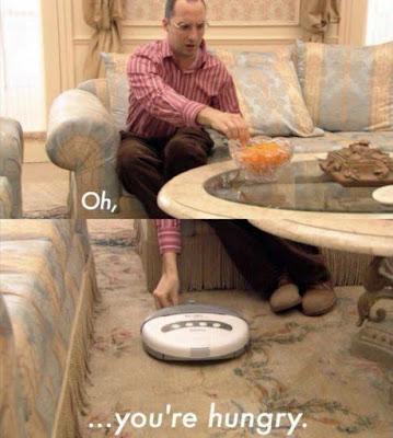 Dummer Mann füttert seinen Staubsauger im Wohnzimmer ulkig