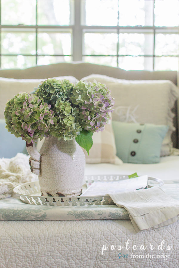 hydrangeas in a crackled white pitcher on a white metal tray