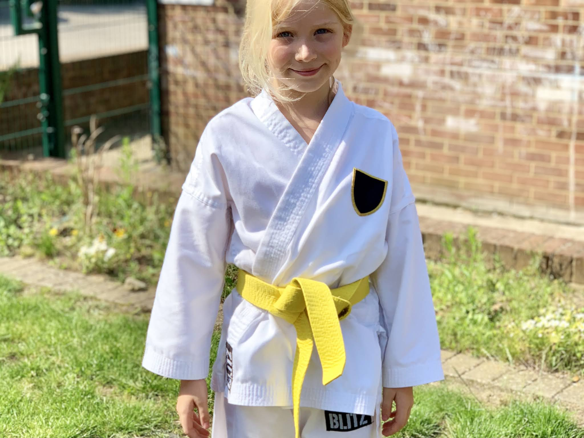 A young girl in a white Karate Gi after getting her yellow belt