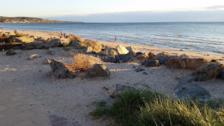 Landscape photograph of a beach on a bay. A path of brick pavers can be seen in the bottom left corner. The bottom right corner shows tufts of grass in the foreground.  The foreground contains sand and is separated from the beach below by a rock wall, the top of which is protruding and divides the photograph horizontally. Beyond the rocks is a sandy beach with people walking along it. The water is light blue, changing to deep blue towards the horizon. In the distance (top left of the photo) the coastline curves and one can see a headland dotted by buildings until the cliffs become too steep. A line of light grey cloud can be seen in the sky approaching from the horizon.