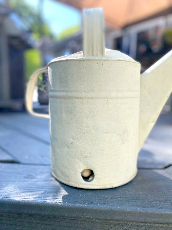 Galvanized watering can with drilled hole.