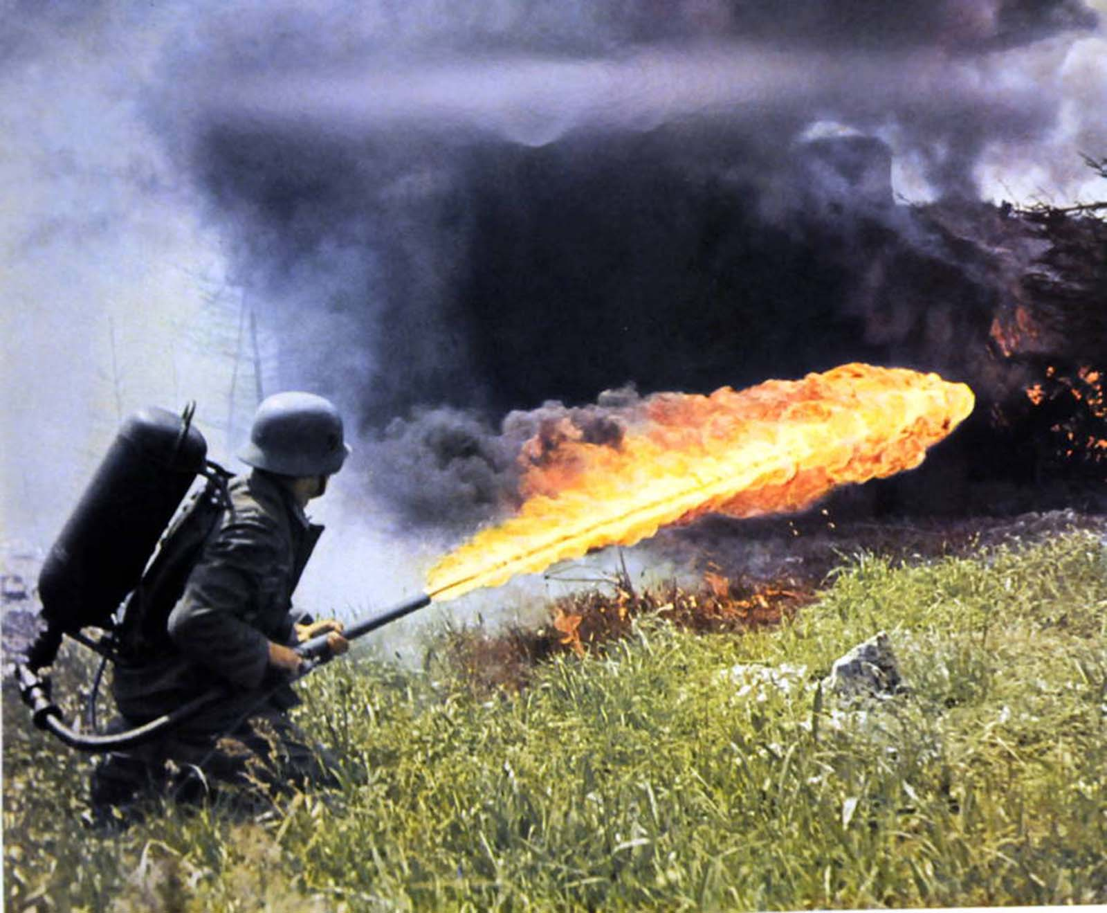 A German solider fires a backpack flamethrower across a field of tall grass in the Soviet Union.