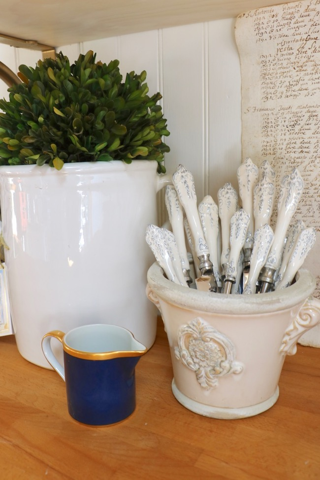 French style medallion decorated flower pot and white scroll flatware are favorite French Country decor