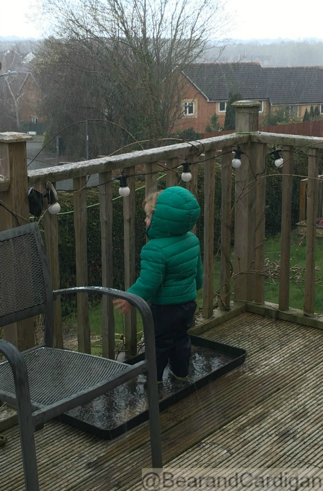 toddler on decking in hail