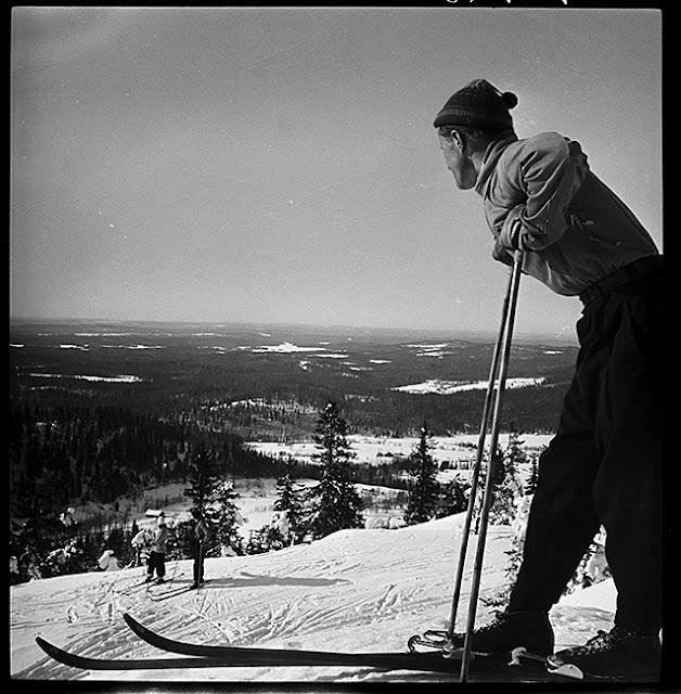 Hiihtäjä nojaa sauvoihin lumisen rinteen päällä ja katsoo maisemaa.
