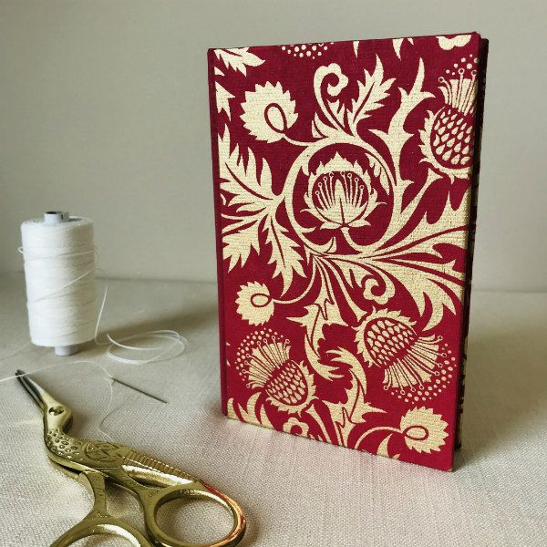 decorative journal with red and metallic gold cover and lined white pages