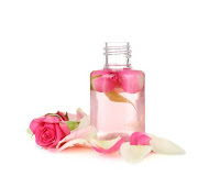 A bottle full of a clear liquid with pink rose petals in an around it