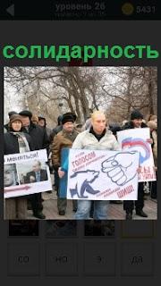 На улице демонстрация людей с плакатами, которые выражают свою солидарность одной из правящих партий