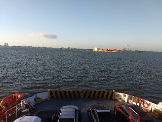 early morning view from upper deck of ferry overlooking cars on deck and a freighter in the distance with Galveston skyline