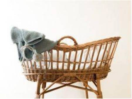 A baby basket with some baby clothes hanging on the side