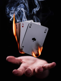 A white hand opened palm up,  with the ace of clubs, ace of hearts and ace of spades floating above it, spread out, facing the viewer -the cards are on fire, with smoke wafting above them - all against a black background