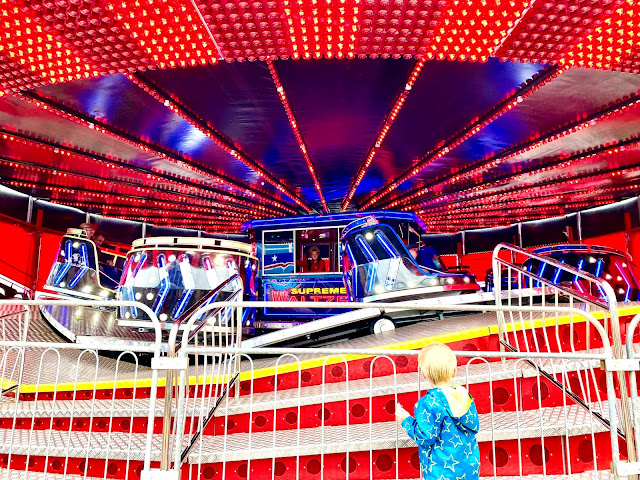 A toddler watching his family of the Waltzer ride