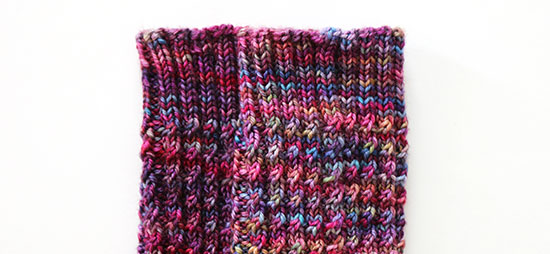 Close-up of the cuffs and legs on a pair of hand knit multi-colored socks with a subtle cable rib pattern against a white background.