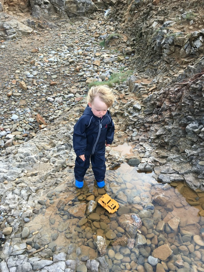 toddler-stood-in-rock-pool-with-toy-lorry
