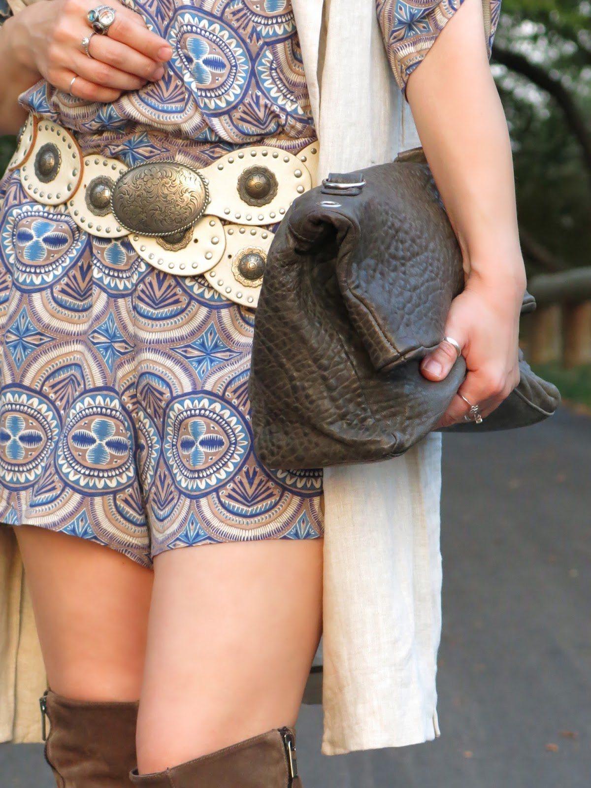 styling a patterned romper with a sleeveless coat, concho belt, and oversized clutch