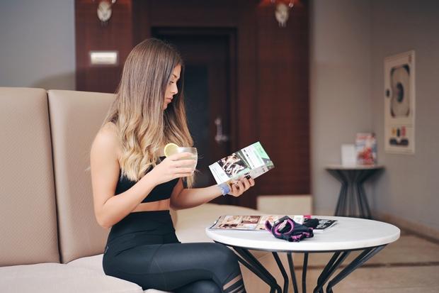 Mulher vestida com roupas esportivas em sua rotina matinal tomando um chá e lendo uma revista