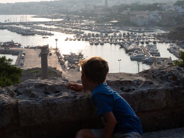 Niño de espaldas asomado sobre el puerto de Santa María de Leuca al atardecer
