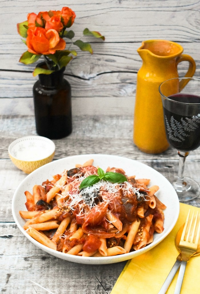 Aubergine tomato pasta in a pasta bowl on a table set with flowers, wine and a water jug