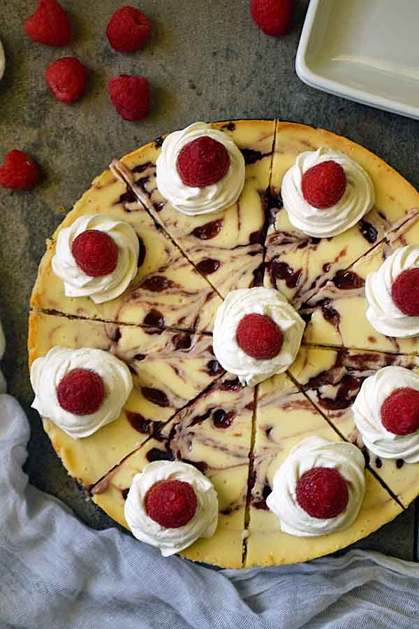 Raspberry White Chocolate Cheesecake decorated with swirls of whipped topping and fresh raspberries, ready to serve