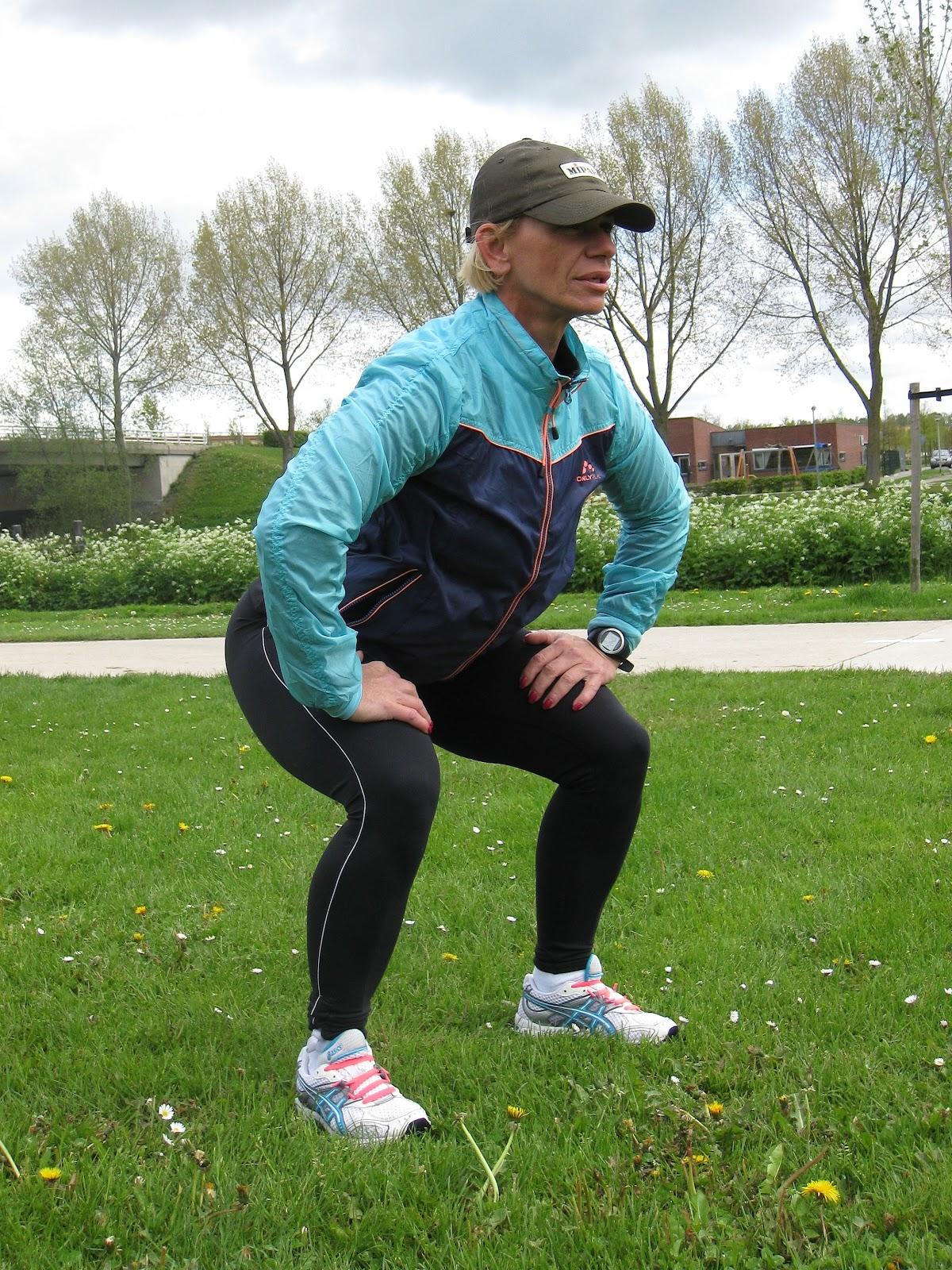 野原で膝屈伸を行うフィットネス姿の女性