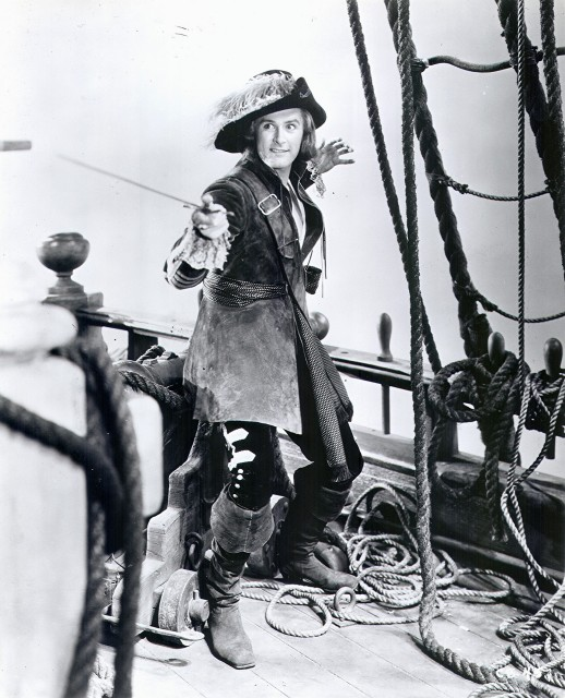Publicity photo of Captain Peter Blood, 1936. Errol Flynn with a crooked smile and an enormous feather in his hat. Freelance Piracy marchmatron.com
