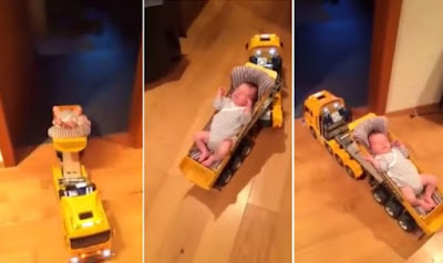 The baby was peacefully sleeping at the back of the toy truck