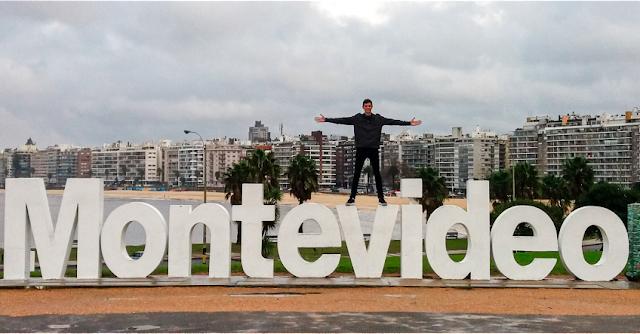 Homem em cima do letreiro escrito Montevideo, com cidade e praia ao fundo