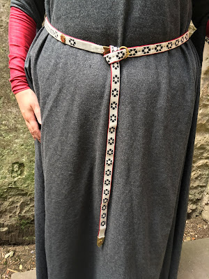 A photo of the waist and legs of a person wearing a grey wool dress with red sleeves and a black, red and white tablet woven belt patterned with flower motifs and brass fittings