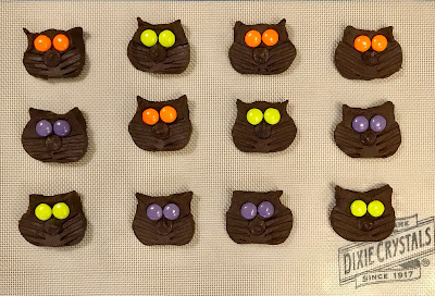 Tray of prepared black cat cookies ready for the oven.