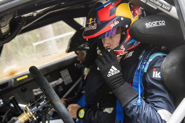 Rally Driver Kalle Rovanpera sat in world rally car with crash helmet and rally suit