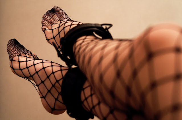 BDSM Dating, legs in fishnets with ankle cuffs. Photo by Artem Labunsky on Unsplash