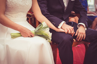 Bride and Groom sitting holding hands