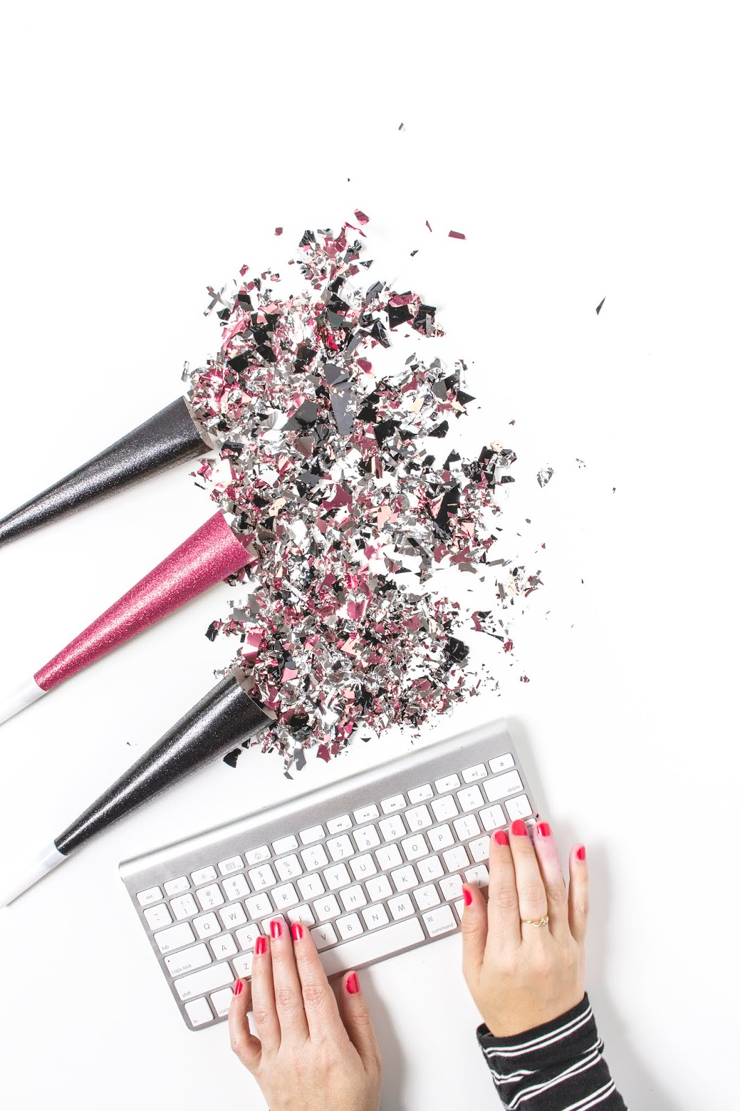 birds eye view of a silver keyboard on a white desk with glitter around it