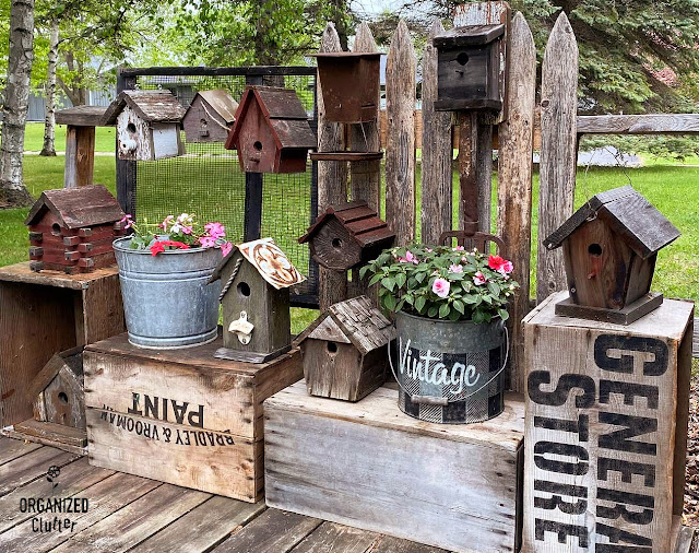 Rustic Birdhouse Display Assembled From Crates, Fence Picket, and a Farm Grain Screen