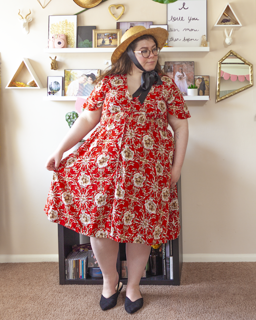 An outfit consisting of a wide brim straw boater hat with a black satin ribbon tied under the chin a bow, a short sleeve red floral dress and black pointed toe slingback flats.