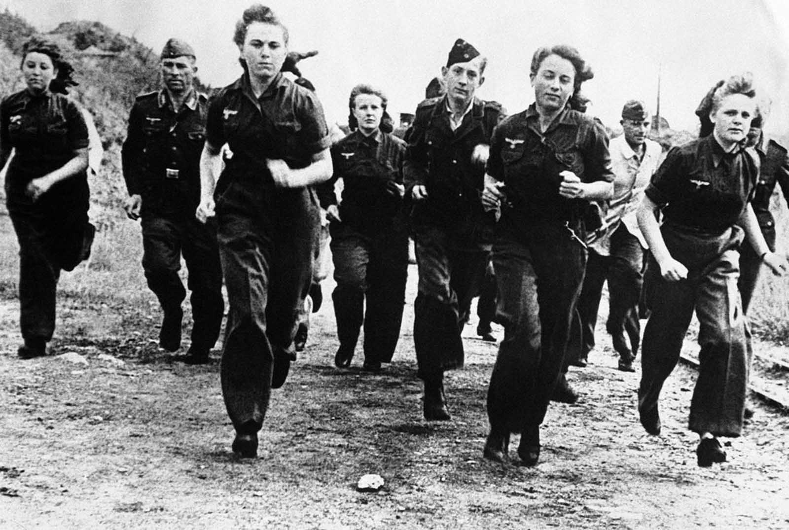 More and more girls are joining the Luftwaffe under Germany's total conscription campaign. They are replacing men transferred to the army to take up arms instead of planes against the advancing allied forces. Here, German girls are shown in training with men of the Luftwaffe, somewhere in Germany, on December 7, 1944.