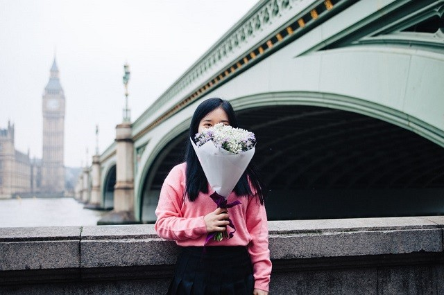 woman london pink shirt holding a bouquet of flowers covering her face