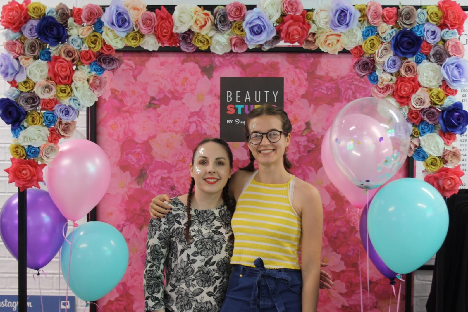 Abbey and Kirstie stand in front of a floral photo booth