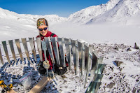 UAF researcher Anna Liljedahl puts up a wind shield around a rain gauge she installed on Jarvis Glacier. (Credit: UAF photo by Todd Paris) Click to Enlarge.