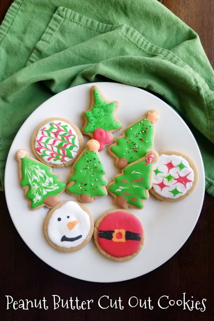 peanut butter cookies cut in Christmas shapes and decorated with royal icing