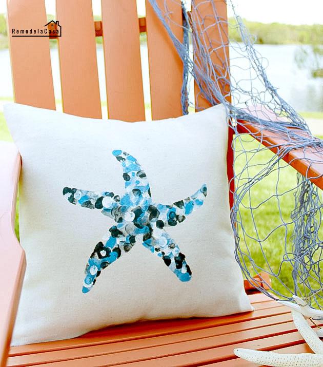 envelope pillow with thumbprint design on orange Adirondack chair by the lake