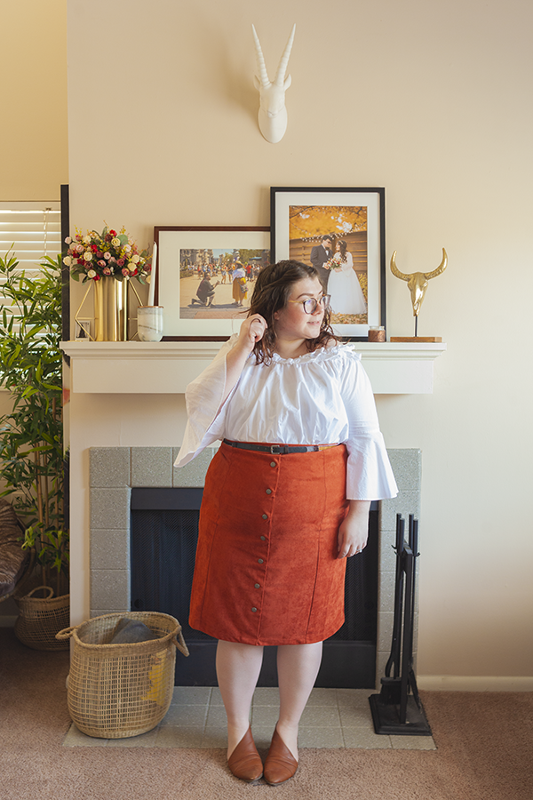 An outfit consisting of a ruffled white off the shoulder blouse with 3/4 bell sleeves, tucked into button down burnt orange midi skirt and brown d'orsay flats.