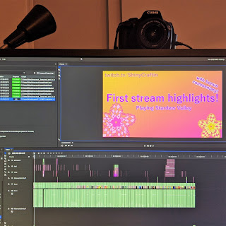 A computer monitor with Canon DSLR setup behind. The monitor has video editing software, Hitfilm Express open and exporting. The timeline at the bottom of the screen shows a heavily cut video.