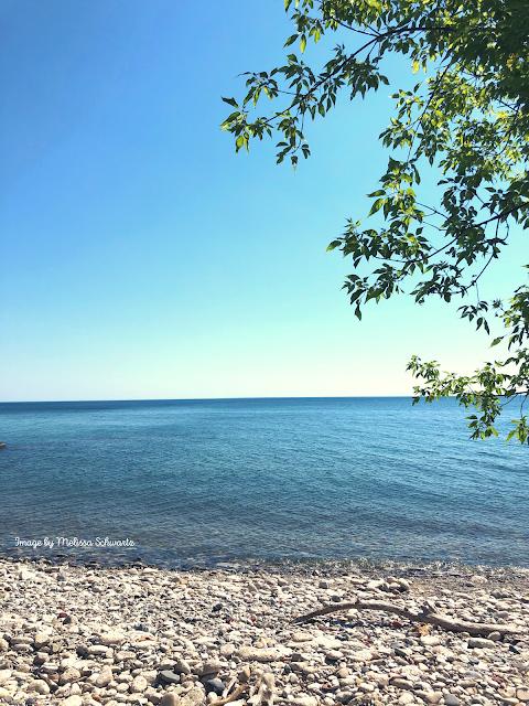 Lake Michigan gently laps upon a rocky beach at Sheridan Park in Cudahy, Wisconsin.
