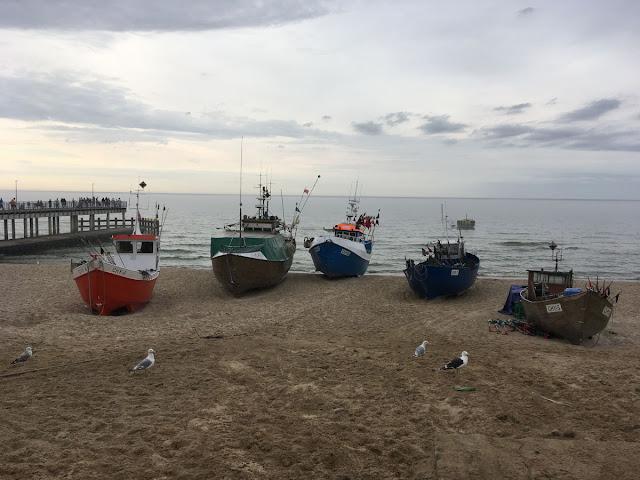 Chłopy nad Morzem Bałytyckim kutry rybackie obok molo przy plaży.