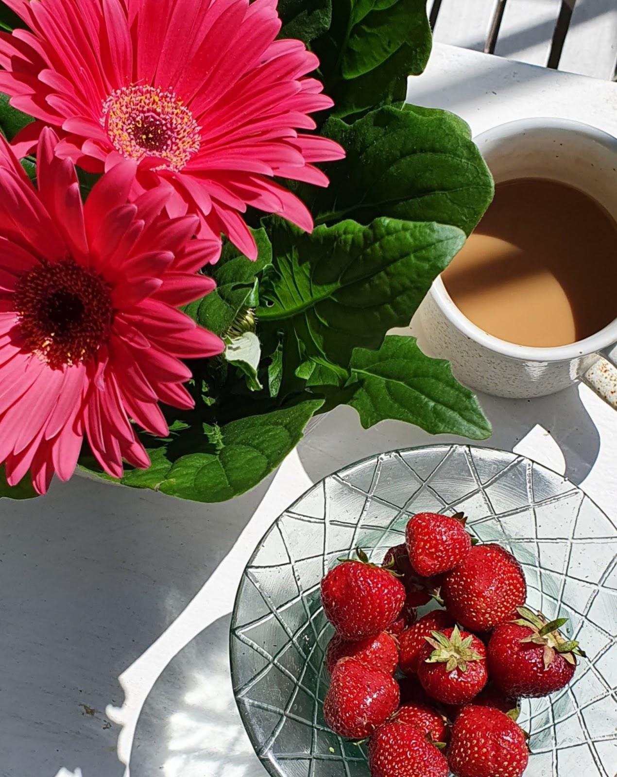 pinkki kukka ja mansikoita astiassa