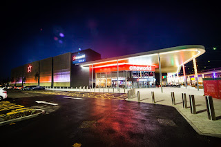 A zoomed out picture of a rectangular white building in the night with a white logo saying Cineworld in white font with a red star logo below it on a dark background.