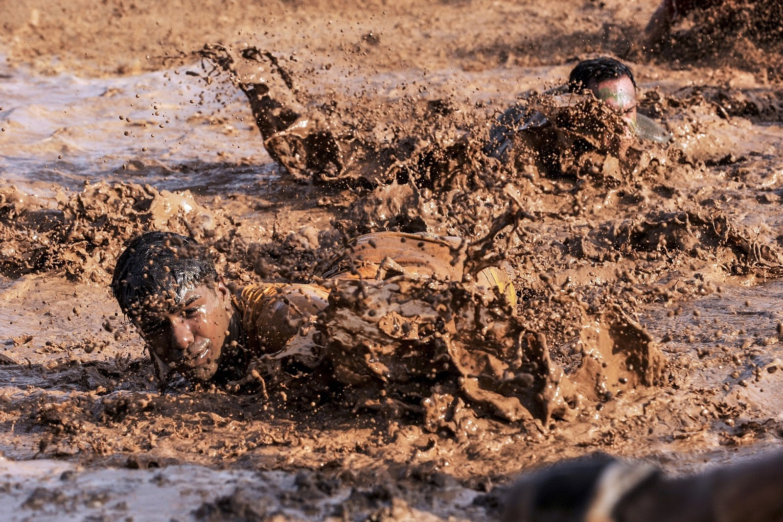 army soldier crawls through a mud pit to illustrate a blog post about army basic training