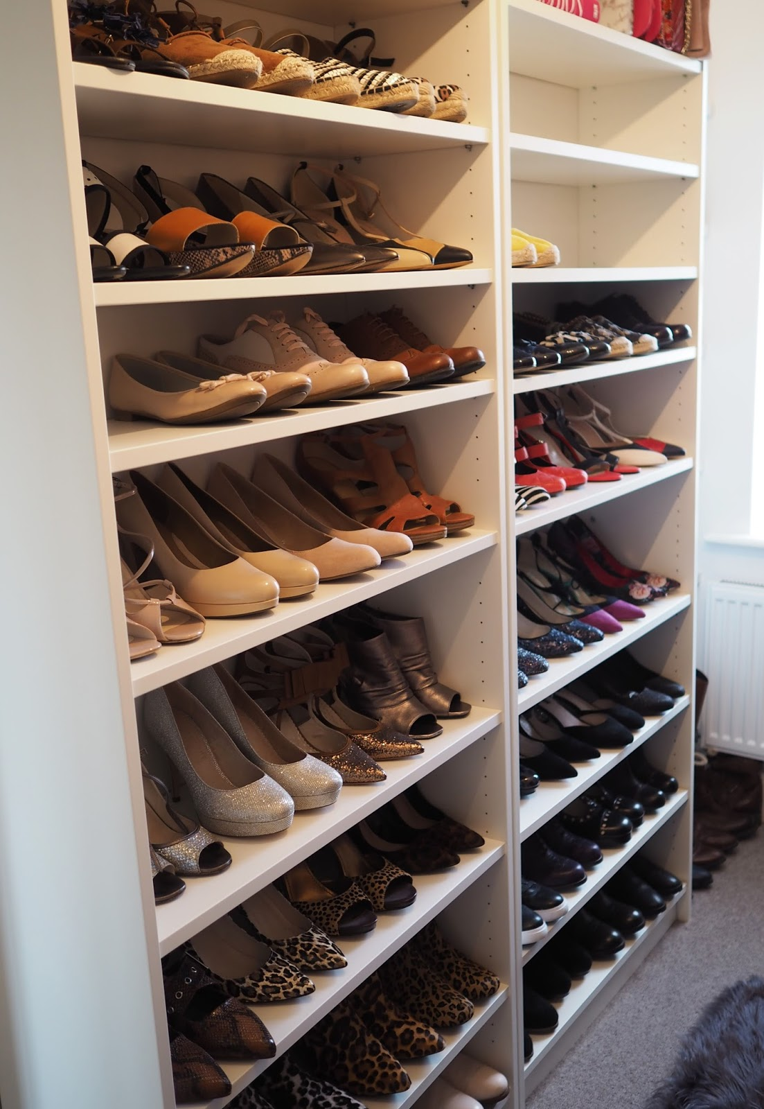 Walk in closet with white Ikea Billy bookcase as shoe shelf storage