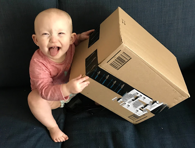 A baby pulling a cheeky face holding a medium size Amazon box
